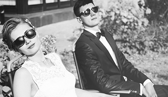 trendy bride and groom in sun glasses